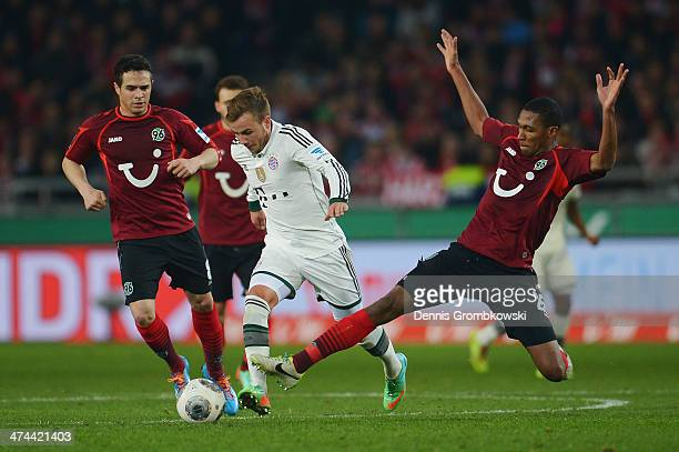 Mario Goetze of FC Bayern Muenchen is challenged by Marcelo of Hannover 96 during the Bundesliga match between Hannover 96 and FC Bayern Muenchen at...