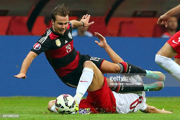 Mario Goetze of Germany battles for the ball with Grzegorz Krychowiak of Poland during of the EURO 2016 Group D qualifying match between Poland and...