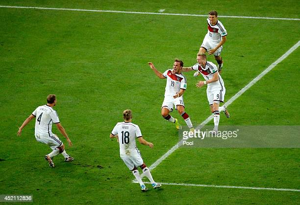 Mario Goetze of Germany celebrates scoring his team's first goal in extra time with Benedikt Hoewedes, Thomas Mueller, Andre Schuerrle and Toni Kroos...