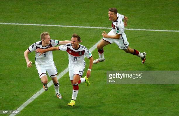 Mario Goetze of Germany celebrates scoring his team's first goal in extra time with Andre Schuerrle and Thomas Mueller during the 2014 FIFA World Cup...