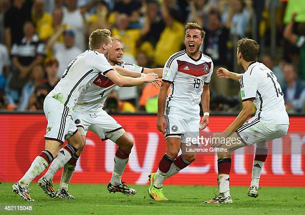 Mario Goetze of Germany celebrates scoring his team's first goal in extra time with teammates Andre Schuerrle Benedikt Hoewedes and Thomas Mueller...
