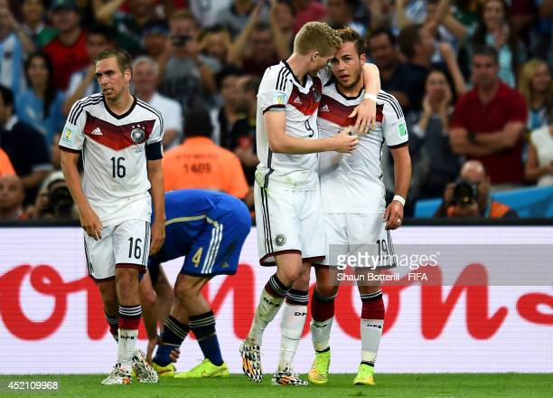 Mario Goetze of Germany celebrates scoring his team's first goal with his teammates Philipp Lahm and Andre Schuerrle during the 2014 FIFA World Cup...