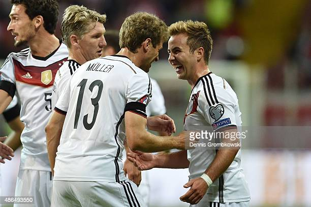 Mario Goetze of Germany celebrates scoring his team's second goal with Bastian Schweinsteiger and Thomas Mueller during the EURO 2016 Qualifier Group...