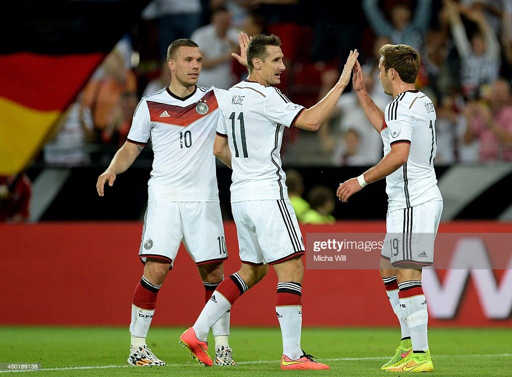 Mario Goetze (R) of Germany celebrates with Lukas Podolski (L) and Miroslav Klose of Germany after scoring his team's fifth goal during the international friendly match between Germany and Armenia at Coface Arena on June 6, 2014 in Mainz, Germany.