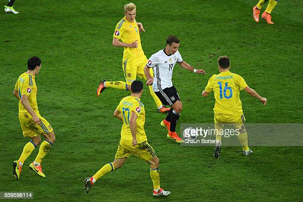 Mario Goetze of Germany controls the ball under pressure of Ukraine defense during the UEFA EURO 2016 Group C match between Germany and Ukraine at...