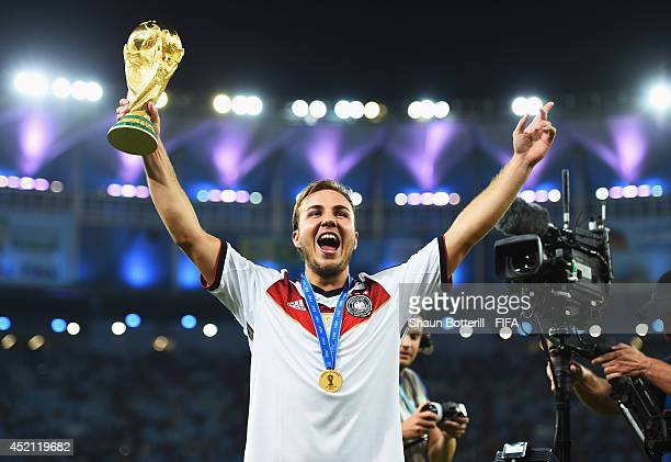Mario Goetze of Germany holds up the World Cup trophy after the 1-0 win in the 2014 FIFA World Cup Brazil Final match between Germany and Argentina...