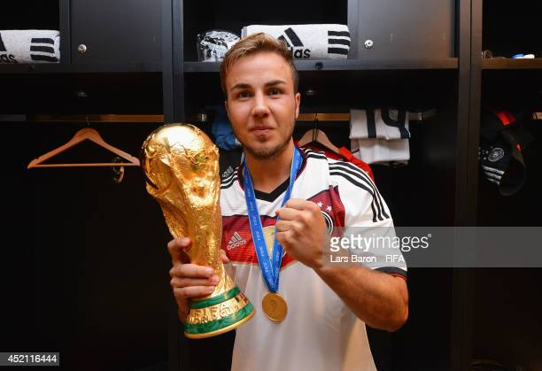 Mario Goetze of Germany holds up the World Cup trophy in the Germany dressing room after the 2014 FIFA World Cup Brazil Final match between Germany...