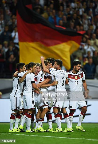 Mario Goetze of Germany is mobbed by team mates after scoring his teams third goal during the EURO 2016 Qualifier Group D match between Germany and...