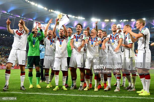 Mario Goetze of Germany lifts the World Cup trophy to celebrate with his teammates after the 2014 FIFA World Cup Brazil Final match between Germany...