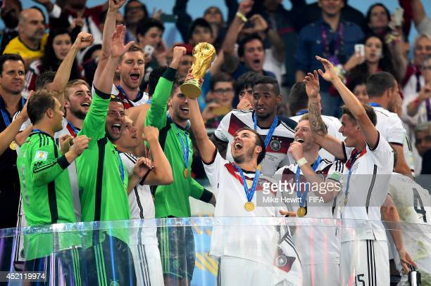 Mario Goetze of Germany lifts the World Cup trophy to celebrate with his teammates during the award ceremony after the 2014 FIFA World Cup Brazil...