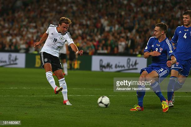 Mario Goetze of Germany scores the first team goal againts Pol Johannus Justinusen of Faeroe Islands and his team mate Rogvi Baldvinsson during the...