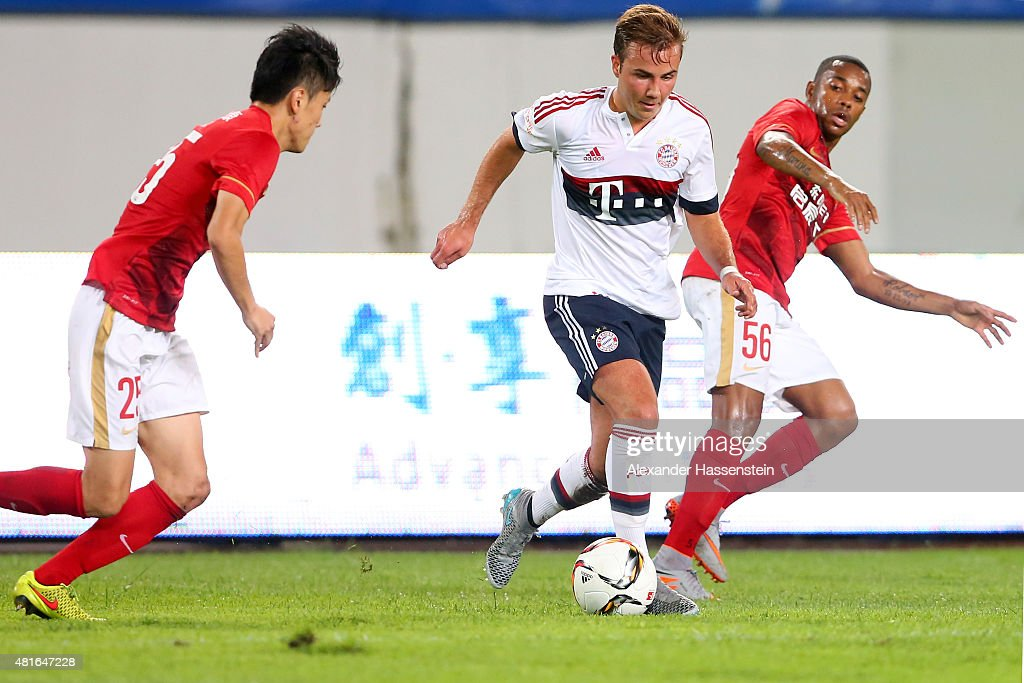 Mario Goetze of Muenchen battles for the ball with Zou Zheng (L) of Guangzhou and his team mate during the international friendly match between FC Guangzhou Evergrande Taobao FC and FC Bayern Muenchen of the Volkswagen Cup Guangzhou at Tianhe Stadium on July 23, 2015 in Guangzhou, China.