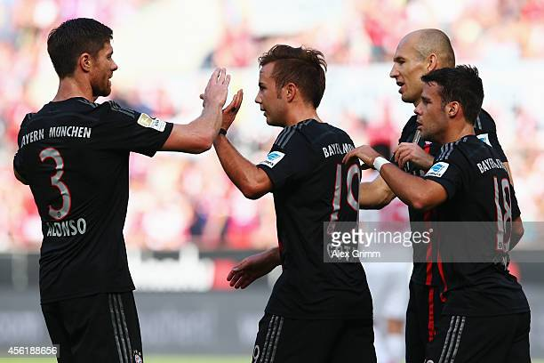 Mario Goetze of Muenchen celebrates his team's first goal with team mates Xabi Alonso Arjen Robben and Juan Bernat during the Bundesliga match...
