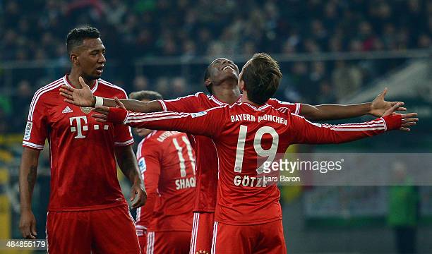 Mario Goetze of Muenchen celebrates with team mate David Alaba after scoring his teams first goal during the Bundesliga match between Borussia...