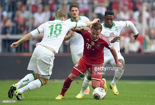 Mario Goetze of Muenchen is challenged by Felix Kroos and Eljero Elia of Bremen during the Bundesliga match between Bayern Muenchen and Werder Bremen...