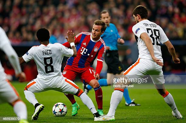 Mario Goetze of Muenchen is challenged by Fred and Sergiy Kryvtsov of Donetsk during the UEFA Champions League Round of 16 second leg match between...