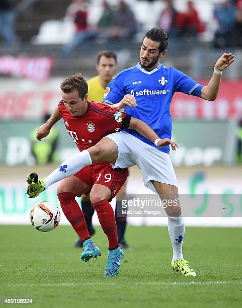 Mario Goetze of Muenchen is challenged by Mario Vrancic of Darmstadt during the Bundesliga match between SV Darmstadt 98 and FC Bayern Muenchen at...