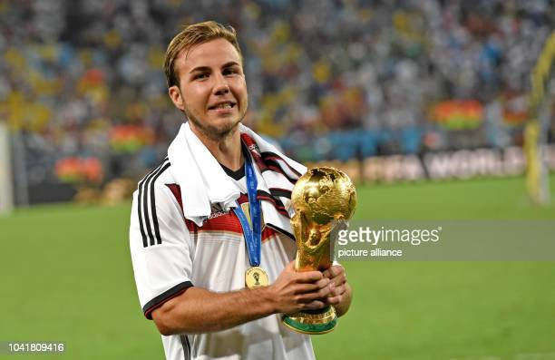 Mario Goetze of Germany poses with the World Cup trophy after winning the FIFA World Cup 2014 final soccer match between Germany and Argentina at the...