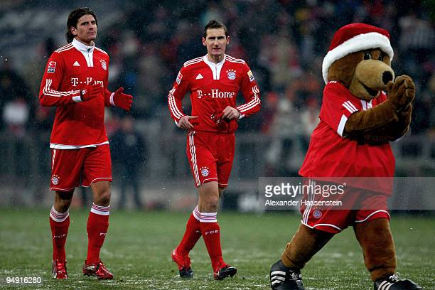 Mario Gomez and his team mate Miroslav Klose of Muenchen celebrate with mascott Berni after the Bundesliga match between Bayern Muenchen and Hertha...