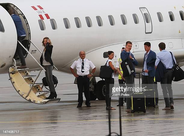 Mario Gomez and Holger Badstuber of Germany board a jet after they arrive at Frankfurt Airport following Germany's defeat to Italy in the semifinal...