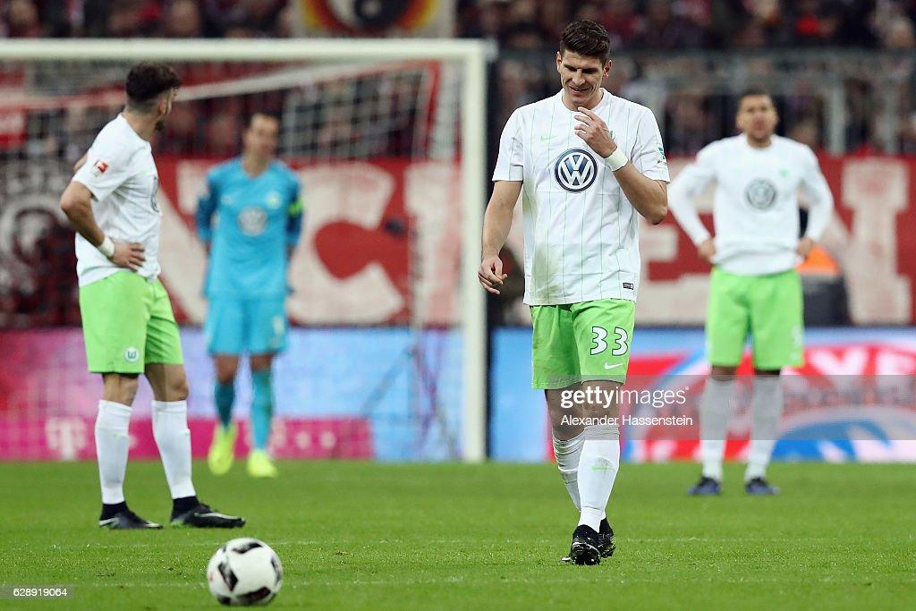 Mario Gomez and team mates of Wolfsburg react after Robert Lewandowski of Muenchen scores his team's third goal during the Bundesliga match between Bayern Muenchen and VfL Wolfsburg at Allianz Arena on December 10, 2016 in Munich, Germany.