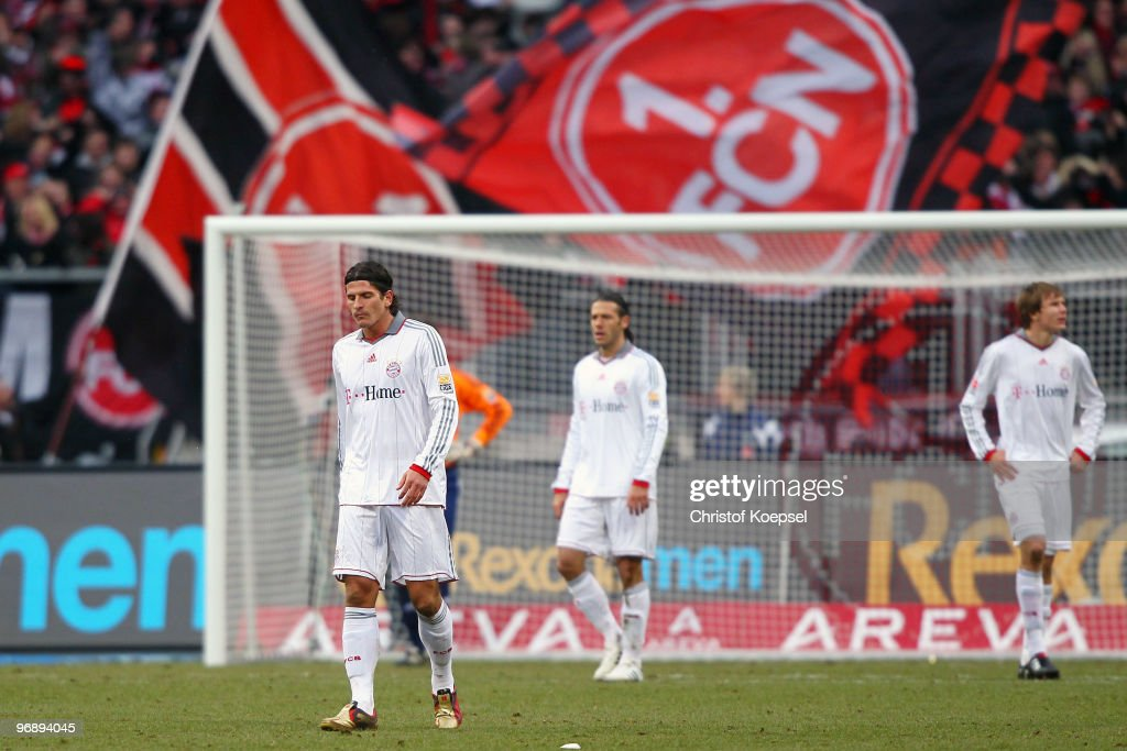 Mario Gomez, Martin Demichelis and Holger Badstuber of Bayern look dejected after receiving the first goal of Nuernberg during the Bundesliga match between 1. FC Nuernberg and FC Bayern Muenchen at Easy Credit Stadium on February 20, 2010 in Nuremberg, Germany.