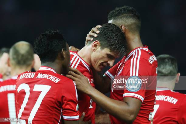 Mario Gomez of Bayern Muenchen celebrates with David Alaba and Jerome Boateng as he scores their third goal during the DFB Cup Final match between FC...