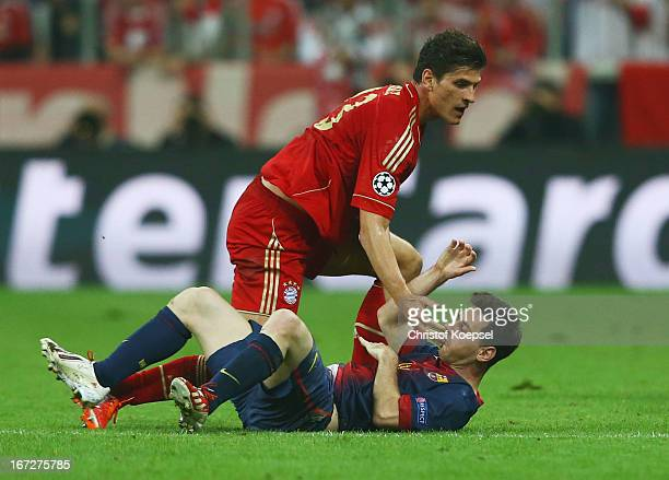 Mario Gomez of Bayern Muenchen clashes with Lionel Messi of Barcelona during the UEFA Champions League Semi Final First Leg match between FC Bayern...