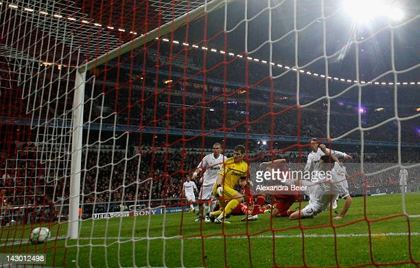 Mario Gomez of Bayern Muenchen scores his first goal against goalkeeper Iker Casillas and Alvaro Arbeloa of Real Madrid during the UEFA Champoins...