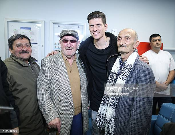 Mario Gomez of Besiktas Football Club poses for a photograph with old people during their visit to Darulaceze Institute in Istanbul Turkey on...