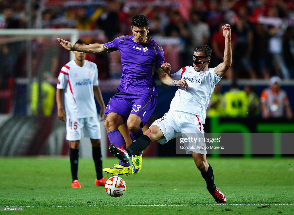 Mario Gomez of Fiorentina is tackled by Grzegorz Krychowiak of Sevilla during the UEFA Europa League Semi Final first leg match between FC Sevilla and ACF Fiorentina at Estadio Ramon Sanchez Pizjuan on May 7, 2015 in Seville, Spain.