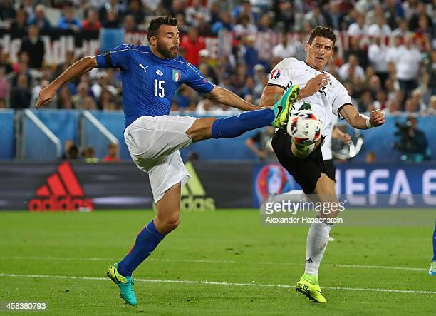 Mario Gomez of Germany and Andrea Barzagli of Italy compete for the ball during the UEFA EURO 2016 quarter final match between Germany and Italy at...