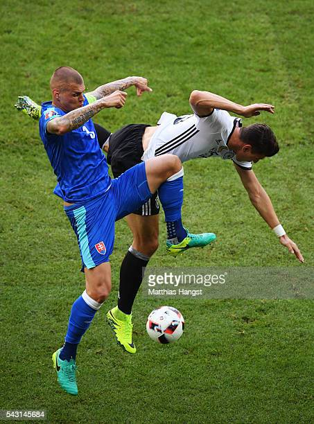 Mario Gomez of Germany and Martin Skrtel of Slovakia compete for the ball during the UEFA EURO 2016 round of 16 match between Germany and Slovakia at...