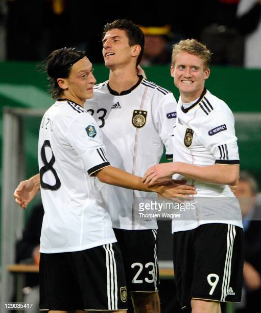 Mario Gomez of Germany celebrates after scoring his teams third goal with his team mates Mesut Oezil and Andre Schuerrle during the Euro 2012...