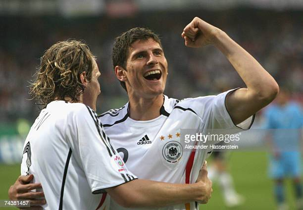Mario Gomez of Germany celebrates scoring the 5th goal with his team mate Marcell Jansen during the UEFA EURO 2008 qualifier between Germany and San...