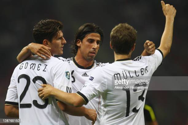 Mario Gomez of Germany celebrates scoring the opening goal with his team mates Sami Khedira and Thomas Mueller during the UEFA EURO 2012 Group A...