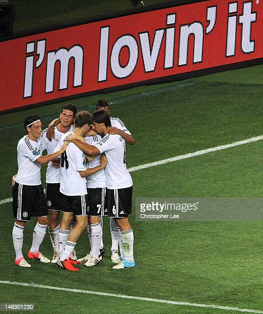 Mario Gomez of Germany celebrates scoring their second goal with team mates during the UEFA EURO 2012 group B match between Netherlands and Germany...