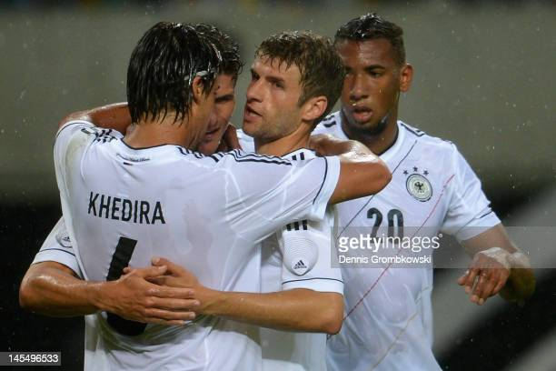Mario Gomez of Germany celebrates with teammates Sami Khedira, Jerome Boateng and Thomas Mueller after scoring his team's opening goal during the...