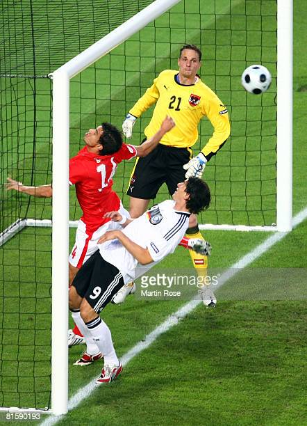 Mario Gomez of Germany misses a chance against Gyorgy Garics and goalkeeper Juergen Macho of Austria during the UEFA EURO 2008 Group B match between...