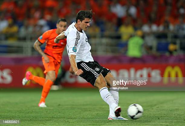 Mario Gomez of Germany scores the opening goal during the UEFA EURO 2012 group B match between Netherlands and Germany at Metalist Stadium on June 13...