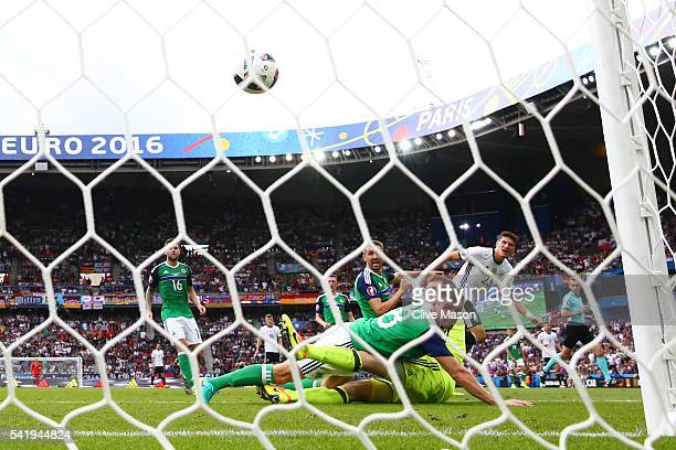 Mario Gomez of Germany scores the opening goal past Michael McGovern and Aaron Hughes of Northern Ireland during the UEFA EURO 2016 Group C match...