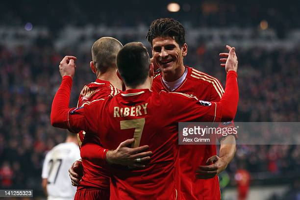 Mario Gomez of Muenchen celebrates his team's sixth goal with team mates Franck Ribery and Arjen Robben during the UEFA Champions League Round of 16...