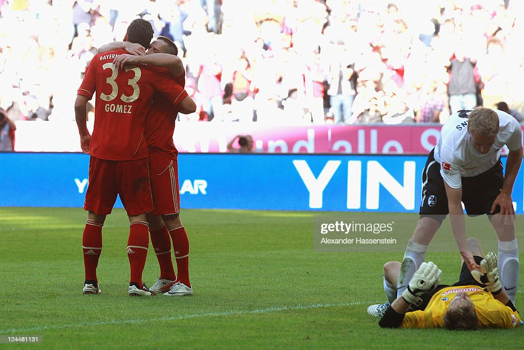 Mario Gomez (L) of Muenchen celebrates scoring the 4th team goal with his team mate Franck Ribery, whilst Freiburg`s keeper Oliver Baumann reacts to his team mate Felix Bastians during the Bundesliga match between FC Bayern Muenchen and SC Freiburg at Allianz Arena on September 10, 2011 in Munich, Germany.