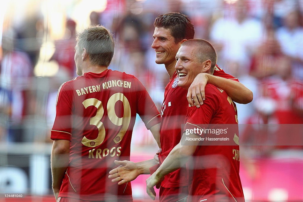 Mario Gomez (C) of Muenchen celebrates scoring the 5th team goal with his team mates Bastian Schweinsteiger (R) and Toni Kroos (L) during the Bundesliga match between FC Bayern Muenchen and SC Freiburg at Allianz Arena on September 10, 2011 in Munich, Germany.