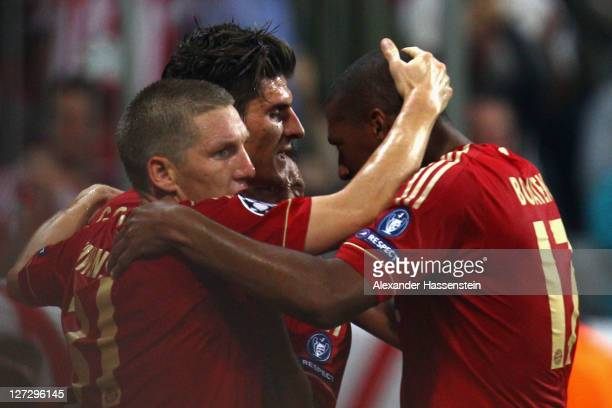 Mario Gomez of Muenchen celebrates scoring the opening goal with his team mates Bastian Schweinsteiger and Jerome Boateng during the UEFA Champions...