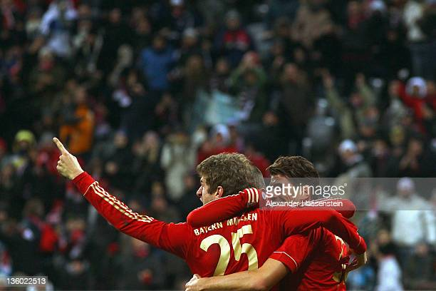 Mario Gomez of Muenchen celebrates scoring the opening goal with his team mates Thomas Mueller and Arjen Robben during the Bundesliga match between...