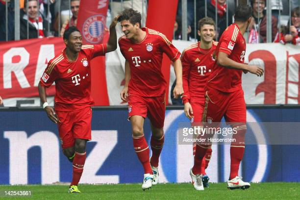 Mario Gomez of Muenchen celebrates scoring the opning goal with his team mate David Alaba during the Bundesliga match between FC Bayern Muenchen and...