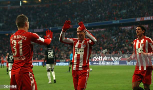 Mario Gomez of Muenchen celebrates scoring the second team goal with his etam mates Bastian Schweinsteiger and Arjen Robben during the Bundesliga...