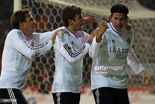 Mario Gomez of Muenchen celebrates with team mates Andreas Ottl and Thomas Mueller after Per Mertesacker of Bremen scored a own goal during the...