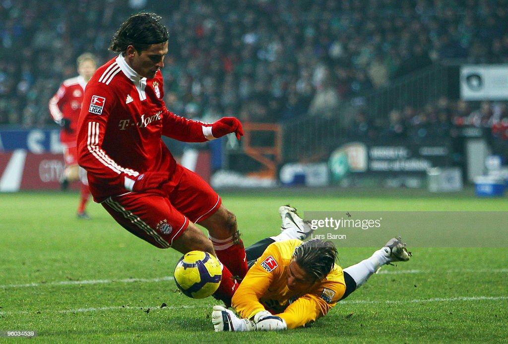 Mario Gomez of Muenchen is challenged by goalkeeper Tim Wiese of Bremen during the Bundesliga match between SV Werder Bremen and FC Bayern Muenchen at Weser Stadium on January 23, 2010 in Bremen, Germany.